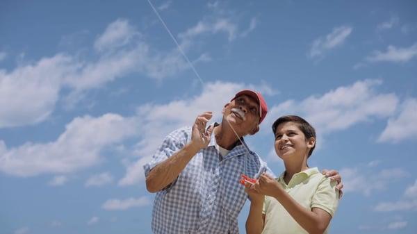18-family-grandpa-teaching-boy-to-fly-kite-slowmotion_szrxquqn__F0004