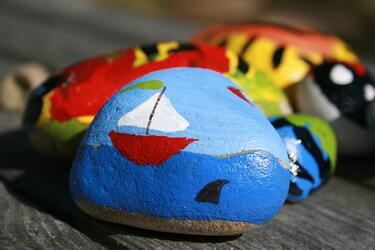A Kindness Rock painted with a boat scene in front of other rocks.